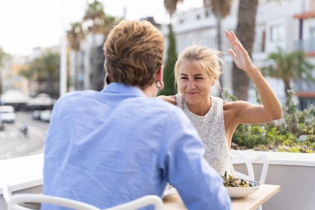 Młoda blondynki kobieta gestykuluje z śmiesznym wyrazem przed młodym mężczyzną, gdy siedzą na tarasie