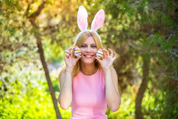 Młoda blondynki kobieta jest ubranym królików ucho iz kolorowymi wielkanocnymi jajkami i robi żartowi