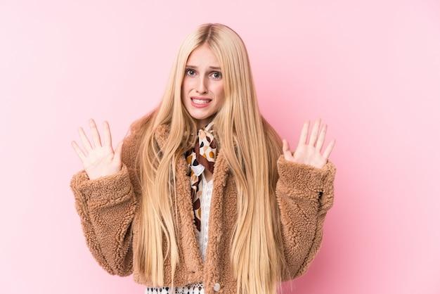 Młoda blondynki kobieta jest ubranym żakiet przeciw menchiom