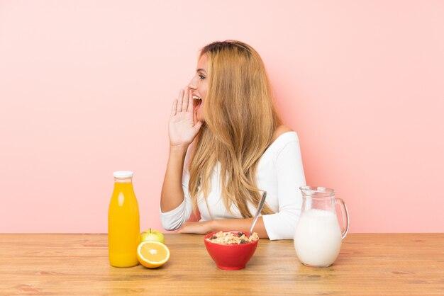 Młoda blondynki kobieta ma śniadania mleko krzyczy z usta szeroko otwarty