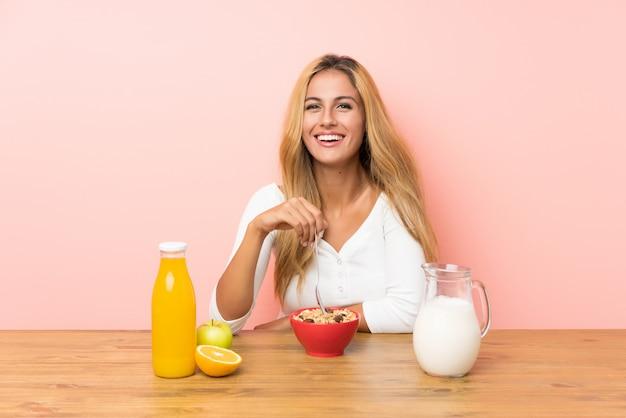 Młoda blondynki kobieta ma śniadania mleko