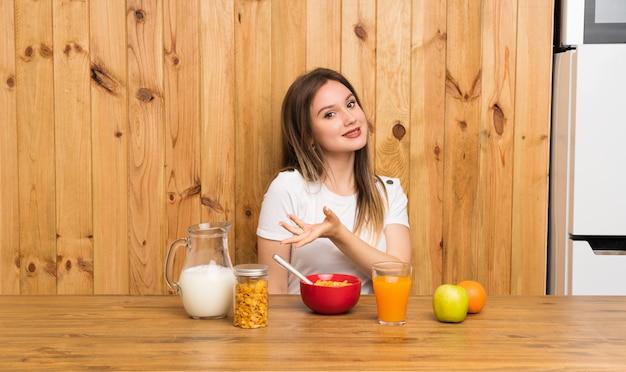 Młoda blondynki kobieta ma śniadanie rozciągać ręki strona dla zapraszać przychodzić
