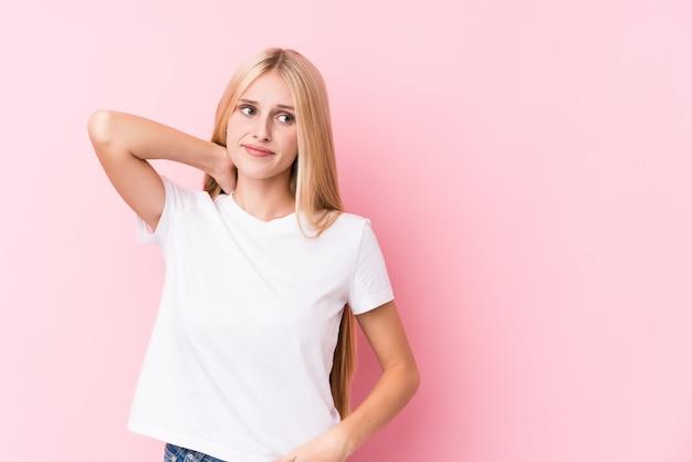 Młoda blondynki kobieta na menchii ścianie dotyka plecy głowa, myśleć i robi wyborowi.