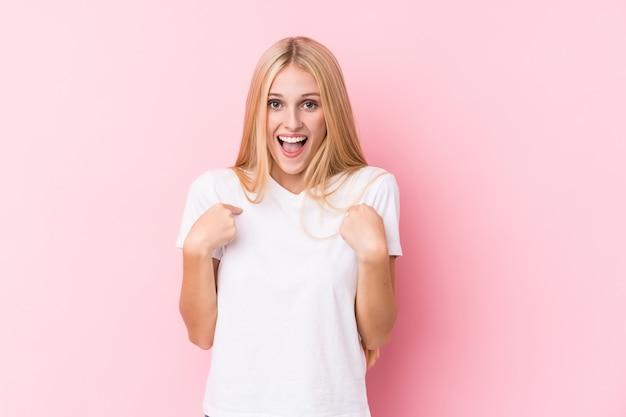 Młoda blondynki kobieta na menchii ścianie zaskakiwał wskazywać z palcem, ono uśmiecha się szeroko.