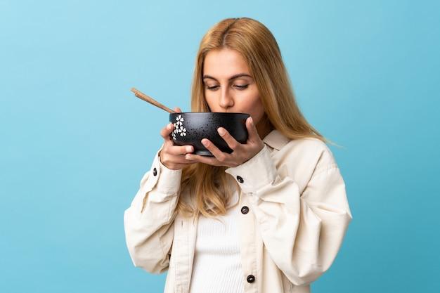 Młoda blondynki kobieta na odosobnionym błękicie trzyma puchar kluski z chopsticks i je je