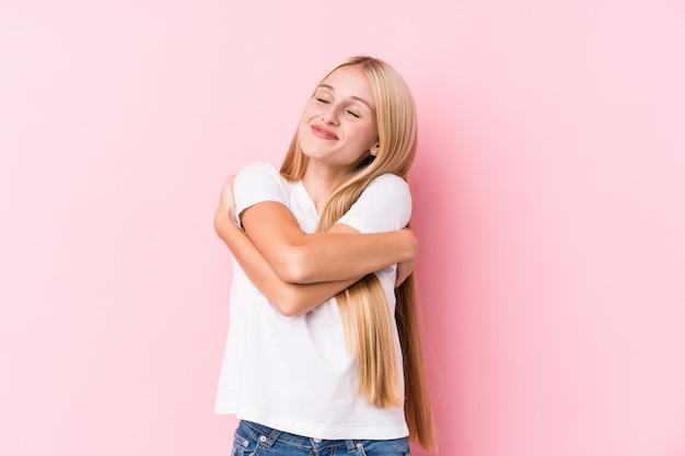 Młoda blondynki kobieta na różowych ścianach ściska, ono uśmiecha się beztroski i szczęśliwy.
