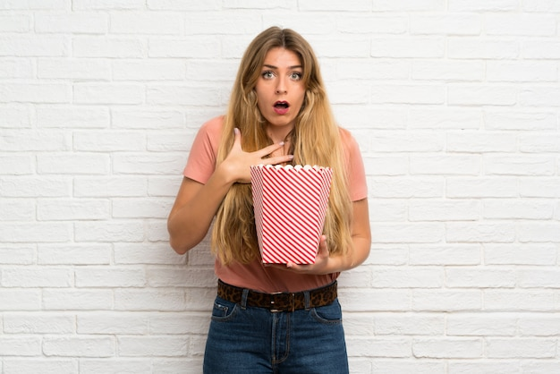 Młoda blondynki kobieta nad białym ściana z cegieł trzyma puchar popcorns
