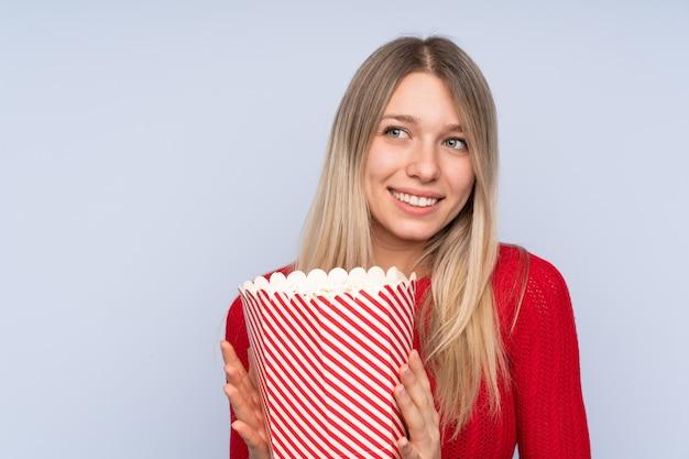 Młoda blondynki kobieta nad błękitem trzyma dużego wiadro popcorns