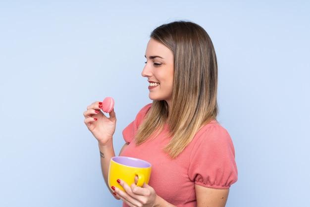 Młoda blondynki kobieta nad odosobnioną błękit ścianą trzyma kolorowych francuskich macarons i filiżankę mleka