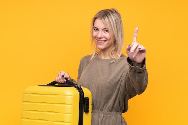 Młoda blondynki kobieta nad odosobnioną kolor żółty ścianą w wakacje z podróży walizką i odliczaniem jeden