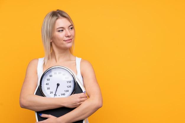 Młoda blondynki kobieta nad odosobnioną kolor żółty ścianą z ważyć maszynę i patrzeć stronę