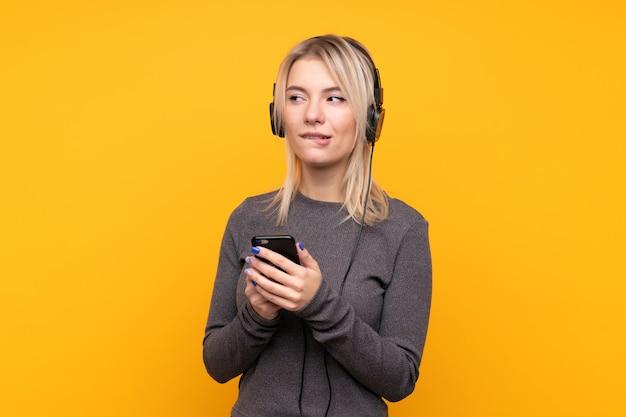 Młoda blondynki kobieta nad odosobnioną kolor żółty ściany słuchającą muzyką z główkowaniem i wiszącą ozdobą