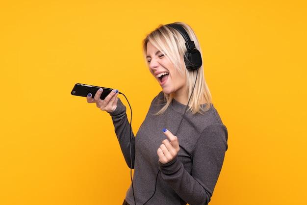 Młoda blondynki kobieta nad odosobnioną kolor żółty ściany słuchającą muzyką z wiszącą ozdobą i śpiewem