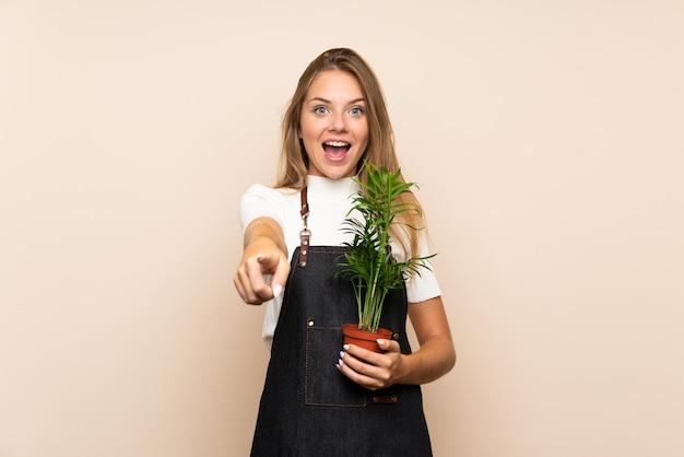 Młoda blondynki kobieta nad odosobnioną ścianą bierze flowerpot i wskazuje przód