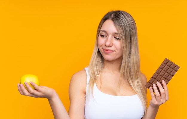 Młoda blondynki kobieta nad odosobnioną ścianą ma wątpliwości podczas gdy brać czekoladową pastylkę w jednej ręce i jabłko w drugiej