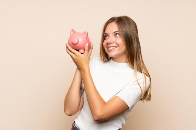 Młoda blondynki kobieta nad odosobnioną ścianą trzyma dużego piggybank