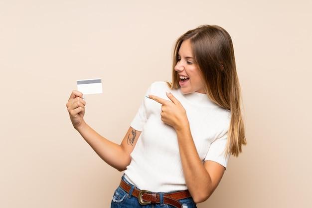 Młoda blondynki kobieta nad odosobnioną ścianą trzyma kartę kredytową