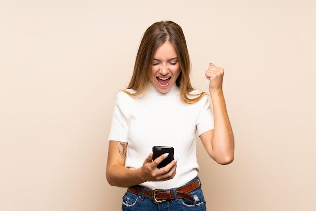 Młoda blondynki kobieta nad odosobnioną ścianą używać telefon komórkowego