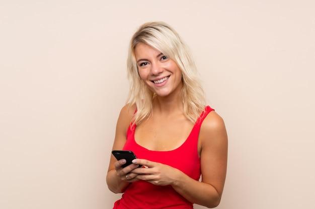 Młoda blondynki kobieta nad odosobnioną ścianą wysyła wiadomość lub emaila z wiszącą ozdobą