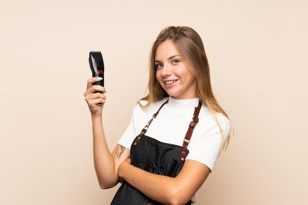 Młoda blondynki kobieta nad odosobnioną ścianą z fryzjera lub fryzjera męskiego suknią i trzymać maszynę do cięcia włosów