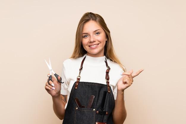 Młoda blondynki kobieta nad odosobnioną ścianą z fryzjera lub fryzjera męskiego suknią i wskazywać stronę