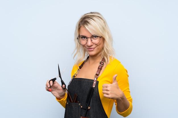 Młoda blondynki kobieta nad odosobnioną ścianą z fryzjera lub fryzjera męskiego suknią z kciukiem up