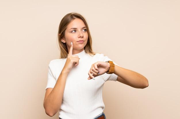 Młoda blondynki kobieta nad odosobnioną ścianą z wristwatch i główkowaniem pomysł