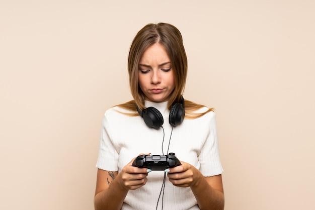 Młoda blondynki kobieta nad odosobnionym tłem bawić się przy gra wideo