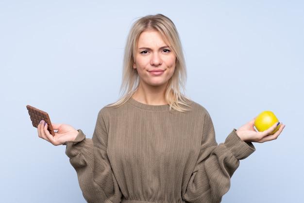 Młoda blondynki kobieta nad odosobnionymi błękitnymi wallhaving wątpi podczas gdy brać czekoladową pastylkę w jednej ręce i jabłko w drugiej