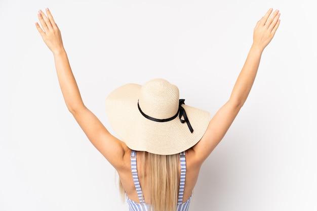 Młoda blondynki kobieta odizolowywająca na biel ścianie w swimsuit i w tylnej pozyci