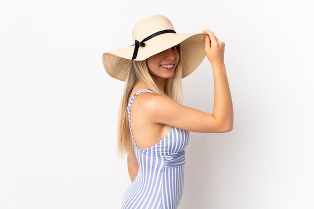 Młoda blondynki kobieta odizolowywająca na biel ścianie w swimsuit w wakacjach letnich