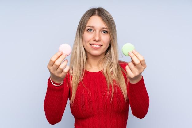 Młoda blondynki kobieta oferuje kolorowych francuskich macarons