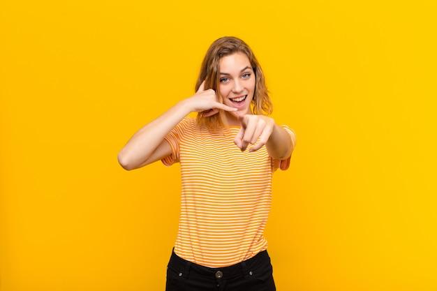Młoda blondynki kobieta ono uśmiecha się radośnie i wskazuje podczas gdy dzwoniący ty później gestykulujesz, opowiada na telefonie przeciw płaskiej kolor ścianie