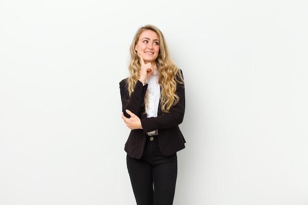 Młoda blondynki kobieta ono uśmiecha się szczęśliwie, marzy lub wątpi, patrzejący strona na biel ścianie