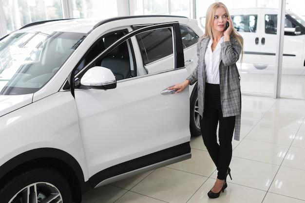 Młoda blondynki kobieta otwiera samochodowego drzwi długi strzał