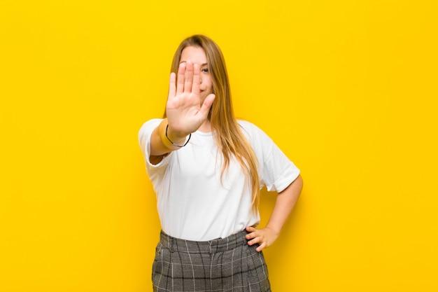 Młoda blondynki kobieta patrzeje poważnego, surowego, niezadowolonego i gniewnego seansu otwartej dłoni robi przerwie, gestykuluje przeciw pomarańcze ścianie