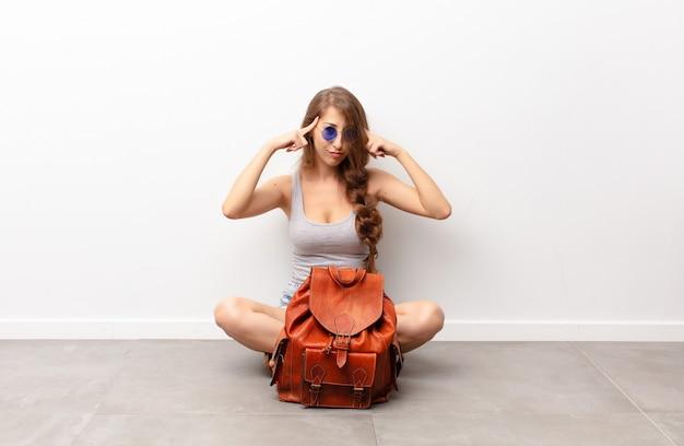 Młoda blondynki kobieta patrzeje skoncentrowaną i mocno zastanawia się nad pomysłem, wyobrażając sobie rozwiązanie wyzwania lub problemu siedzącego na podłodze