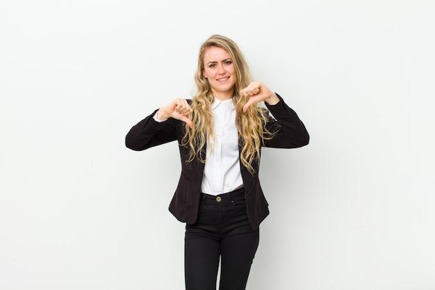 Młoda blondynki kobieta patrzeje smutną, rozczarowaną lub gniewną, pokazuje kciuki w dół w nieporozumieniu, czując się sfrustrowana na białej ścianie