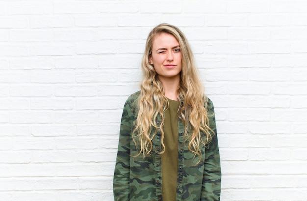 Młoda blondynki kobieta patrzeje szczęśliwa i życzliwa, uśmiecha się i mruga oko z tobą z pozytywnym nastawieniem przeciw ściana z cegieł