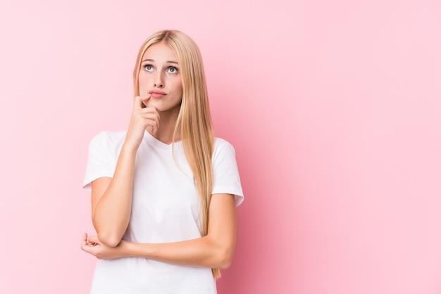 Młoda blondynki kobieta patrzeje z ukosa z różowym i sceptycznym wyrażeniem na różowym tle.