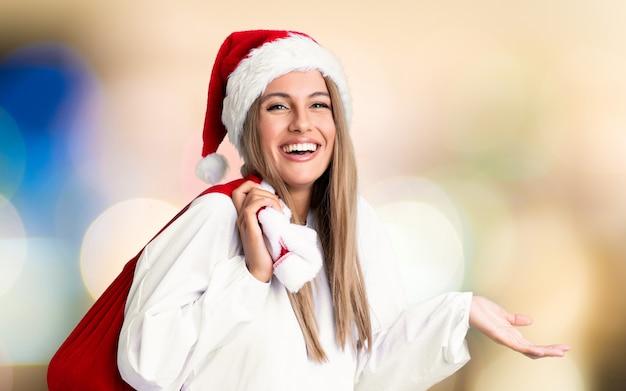 Młoda blondynki kobieta podnosi torbę pełną prezenty w boże narodzenie wakacje