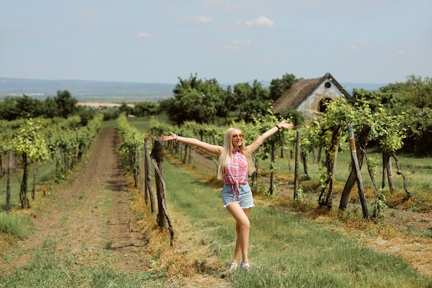 Młoda blondynki kobieta pozuje w winnicach w lato sezonie. wiejski styl wiejski rolnika