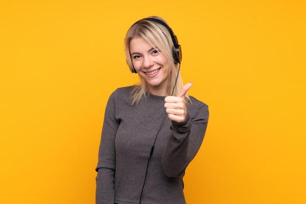 Młoda blondynki kobieta słucha muzykę z kciukiem up i