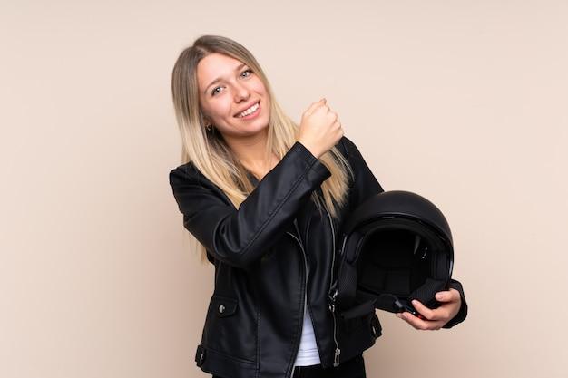 Młoda blondynki kobieta świętuje zwycięstwo z hełmem motocyklowym nad odosobnioną ścianą