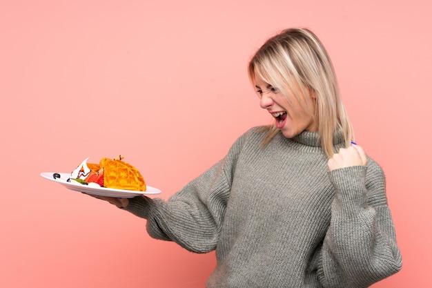 Młoda blondynki kobieta trzyma gofry nad odosobnioną menchii ścianą świętuje zwycięstwo