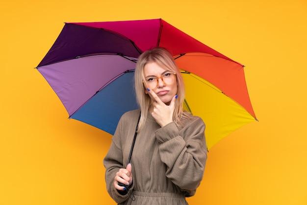 Młoda blondynki kobieta trzyma parasol nad odosobnioną kolor żółty ścianą myśleć pomysł