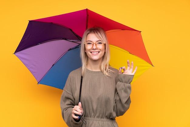 Młoda blondynki kobieta trzyma parasol nad odosobnioną kolor żółty ścianą pokazuje ok znaka z palcami