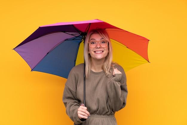 Młoda blondynki kobieta trzyma parasol nad odosobnioną kolor żółty ścianą świętuje zwycięstwo