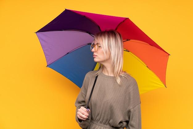 Młoda blondynki kobieta trzyma parasol nad odosobnioną kolor żółty ściany przyglądającą stroną