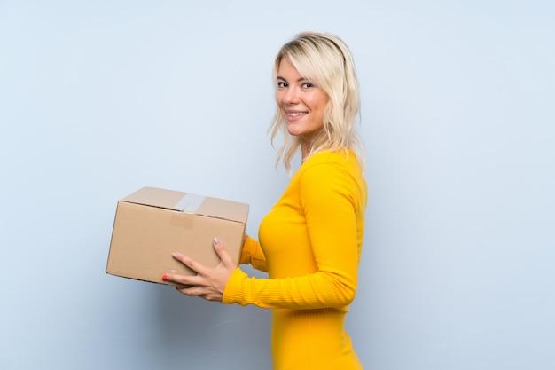 Młoda blondynki kobieta trzyma pudełko, aby przenieść go do innej witryny